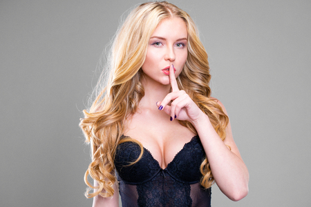 Woman requires silence. Young beautiful blonde girl has put forefinger to lips as sign of silence, isolated on gray background Stock Photo