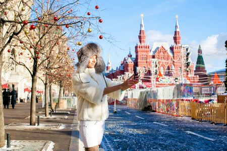 Russian beauty. Portrait of a young beautiful girl in a white hat with a fur hat against a red square in Moscow Stock Photo