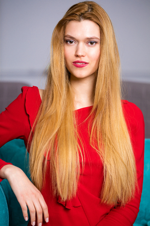 Beautiful young blonde girl in a red sexy dress sitting on a sofa in a beauty salon 스톡 콘텐츠