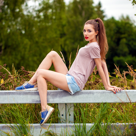 Young beautiful brown haired woman in blue jeans short