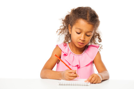Education. Close up portrait of african little girl is sitting at the table with a notebook for drawing, isolated on white background Stock Photo