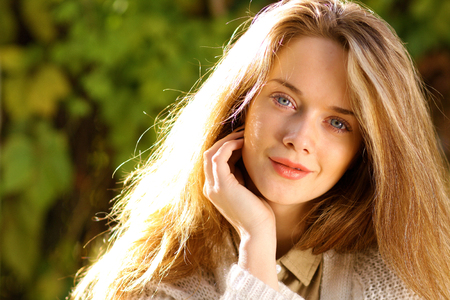 Portrait of beautiful young woman with a blonde hair in autumn