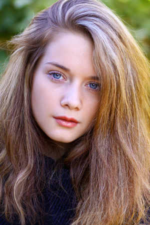 Close up portrait of young blonde beautiful woman in autumn park