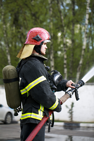 Young Fireman in fire fighting suit spraying water to fire surround
