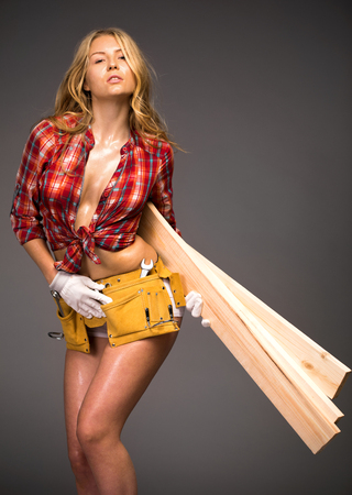 Sexy beautiful blonde girl holding building boards, isolated over gray background