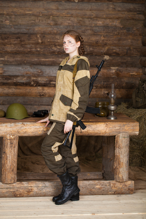 The daughter of a hunter. Young girl in hunting clothes with automatic vitovina on the background of a wooden frame