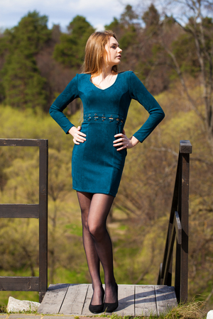 Portrait of a young beautiful girl in a tight short dark turquoise dress posing against a background of a spring park