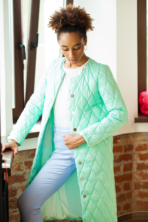 Portrait of an African model woman in a green spring jacket and blue pants Standard-Bild