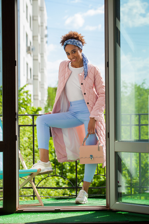 Portrait of an African model woman in pink spring jacket and blue pants posing standing on the balcony (background of the window)