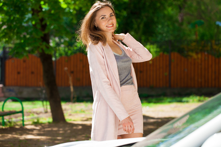 Street fashion. Closeup portrait of a happy young woman in pink skirt and jacket, summer outdoors Stock Photo
