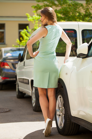 Portrait in full growth of a young beautiful blonde woman in a turquoise dress posing against a white car Imagens