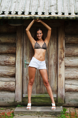 Full body. Young beautiful brunette woman in white jeans shorts posing against wooden wall background