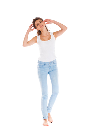 Full length portrait of a smiling cute young woman in blue jeans standing isolated on a white background Stock Photo