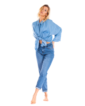 Full length portrait of a smiling cute young blonde woman in blue jeans standing isolated on a white background