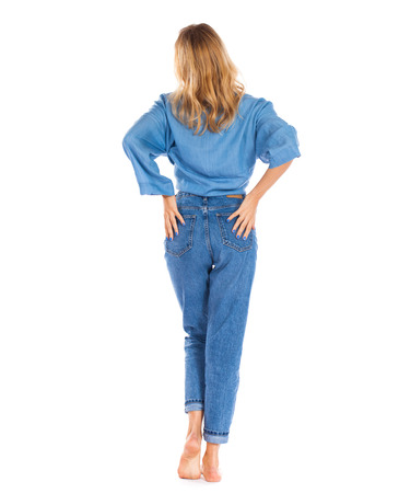 Back view jeans fashion. Full length portrait of young blonde woman in blue jeans standing isolated on a white background Stock Photo