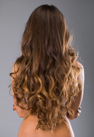 Female Long wavy brunette hair, rear view, isolated on gray background