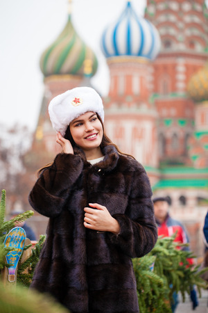 Russian beauty. Portrait of a young beautiful girl in a white hat with a fur hat against a red square in Moscow Stok Fotoğraf