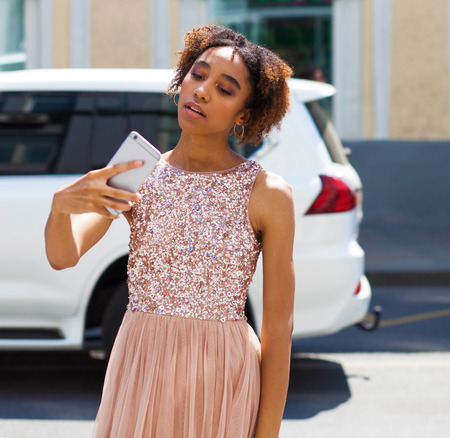 Street fashion model. Portrait of an African young woman in pink dress