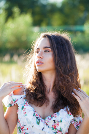 Portrait close up of young beautiful brunette woman in white dress, posing at sunset in the field Stock Photo
