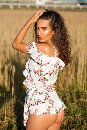 白いドレスを着た若い美しいブルネットの女性の肖像画は、フィールドで日没時にポーズをとります