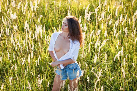 Attractive brunette young woman posing flirty at grass fields, summer outdoor