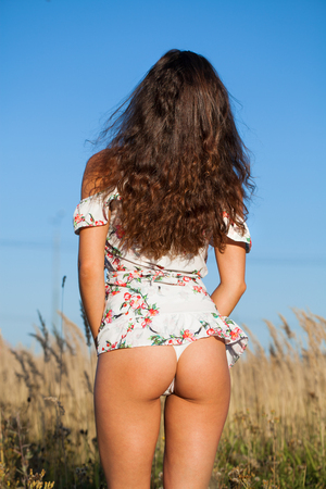 Female thighs and buttocks in white summer dress