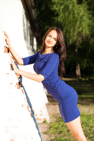 Beautiful young brunette woman in sexy blue dress, against white brick wall, summer outdoors Stock fotó