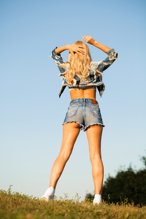 Portrait in full growth, young beautiful sexy blonde woman in blue jeans shorts, summer park outdoor Stock Photo