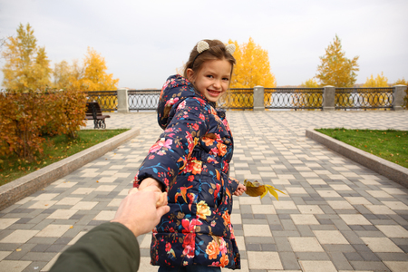 Follow me, Beautiful little girl holds the hand of a father in autumn city park 스톡 콘텐츠