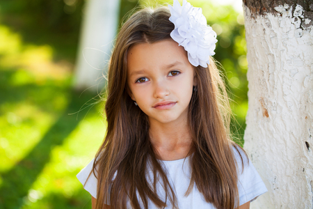 Portrait of a beautiful young brunette little girl, summer outdoors