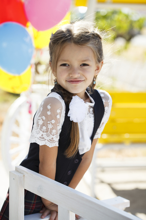 The first of September is the day of knowledge. Portrait of a beautiful first-grader girl in school uniform Foto de archivo