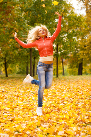 Portrait of happy smiling beautiful young woman, autumn park outdoors