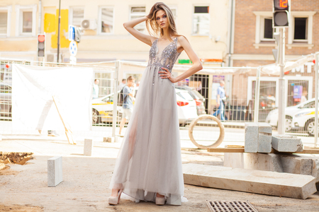 Young beautiful blonde woman in summer white dress on summer street background