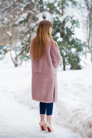 Full length portrait of young beautiful elegant brunette woman wearing fur coat. Fashionable girl walking at the street at winter. Standard-Bild