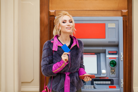 Young happy blonde woman in winter fur coat withdrawing money from credit card at ATM Stock Photo
