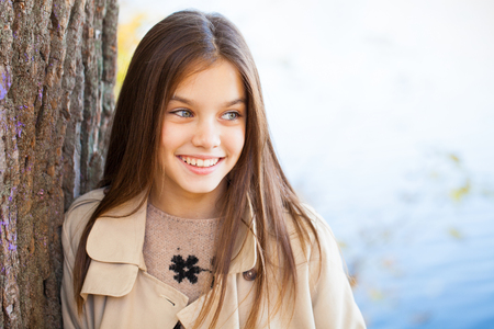 Portrait of a beautiful young brunette little girl, autumn park outdoors