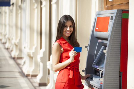 Young happy brunette woman in red dress withdrawing money from credit card at ATM