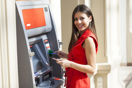 Young happy brunette woman in red dress withdrawing money from credit card at ATM 版權商用圖片 - 112020895