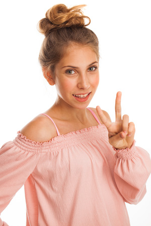 brunette little girl showing victory or peace sign, isolated on white background
