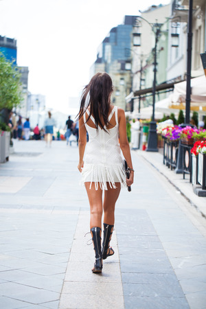 Portrait in full growth, young beautiful brunette woman in white dress walking on the summer street, outdoors Stockfoto