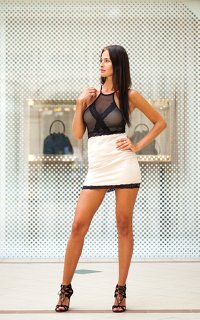Full-length portrait of a young beautiful brunette in a white skirt on the background of a shop window