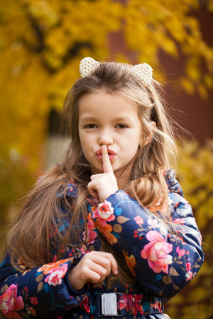 Young beautiful Little girl has put forefinger to lips as sign of silence, autumn park outdoors Archivio Fotografico