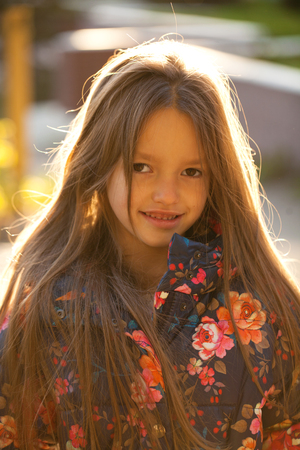 Blonde Hair Beauty. Portrait of a beautiful little girl on the background of summer street Standard-Bild