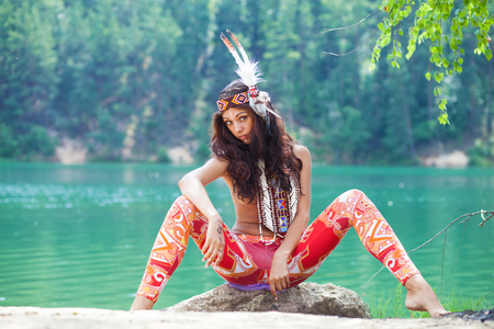 Portrait of a beautiful sexy young woman in Indian costume posing against a forest lake