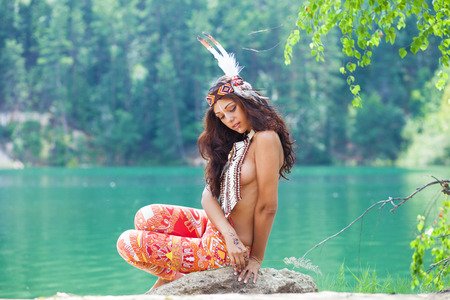 Portrait of a beautiful sexy young woman in Indian costume posing against a forest lake Stock Photo - 112982989