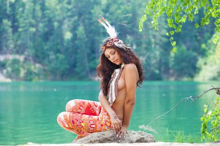 Ritratto di una bellissima giovane donna in costume indiano in posa contro un lago della foresta