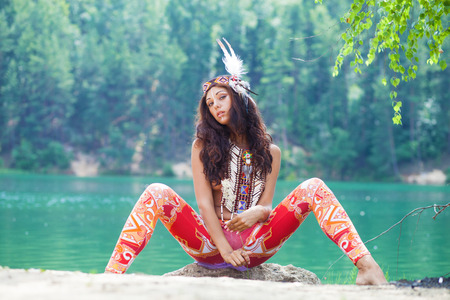 Portrait of a beautiful young woman in Indian costume posing against a forest lake