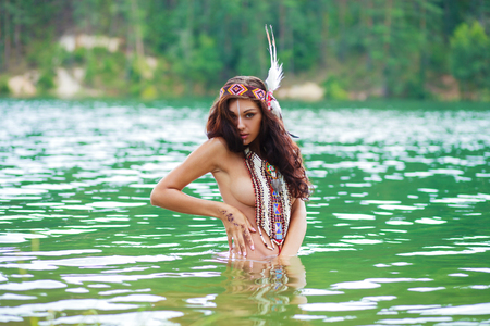 Portrait of a beautiful sexy young woman in a Native American costume posing waist-high in a river