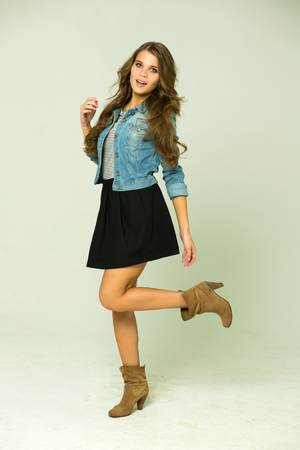 Happy Young brunette woman in a black skirt and blue jeans jacket