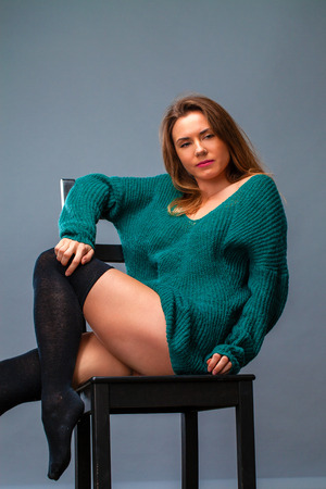 Young beautiful girl in a woolen sweater sitting on a chair in the studio on a gray background background